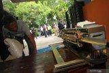 Pekerja mengangkut barang bukti saat penggerebekan rumah produksi jamu kuat ilegal di Babatan Pilang, Surabaya, Jawa Timur, Senin (24/2/2020). Direktorat Reserse Narkoba (Ditresnarkoba) Polda Jawa Timur menangkap tiga orang dalam penggerebekan itu dan mengamankan sejumlah barang bukti beberapa diantaranya alat produksi, jamu kuat siap edar sekitar 50 karton serta bahan baku jamu seberat sekitar 5 kilogram. Antara Jatim/Didik/Zk