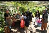 Barista menerima sampah plastik yang ditukarkan dengan kopi di Kampus Unair Banyuwangi, Jawa Timur, Kamis (27/2/2020). Ngopi bayar sampah yang digelar di area kampus oleh mobile cafe itu, selain diharapkan mengedukasi mahasiswa agar tidak membuang sampah sembarangan juga mengenalkan nilai ekonomi dari hasil pengolahan sampah. ANTARA FOTO/Budi Candra Setya/nym.