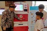 """Direktur Pengelolaan Informasi Administrasi Kependudukan (PIAK) Kementerian Dalam Negeri Tavipiyono (kiri) memberikan penjelasan kepada anak dan orang tuanya cara membuat Kartu Identitas Anak (KIA) menggunakan mesin Anjungan Dukcapil Mandiri (ADM) saat peluncuran di Mal Pelayanan Publik Graha Sewaka Dharma, Denpasar, Bali, Kamis (27/2/2020). Mesin ADM tersebut bagian dari program """"Smart City"""" Denpasar untuk mempermudah dan mempercepat layanan masyarakat dalam pencetakan 23 jenis dokumen kependudukan dan catatan sipil. ANTARA FOTO/Nyoman Hendra Wibowo/nym."""