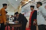 Ketua KPU Pandeglang Ahmad Sujai menandatangani berkas acara pelantikan disaksikan rohaniawan