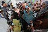 Ketua DPRK Banda Aceh Farid Nyak Umar (kiri) membagikan masker pada warga saat sosialisasi menghadapi ancaman Coronavirus 2019 (COVID - 19) di Desa Beurawe, Banda Aceh, Aceh, Selasa (3/3/2020). Warga diimbau tidak panik dengan ancaman COVID-19 dengan memulai dan meningkatkan pola hidup sehat, lingkungan yang bersih serta menjaga kesehatan tubuh. Antara Aceh/Irwansyah Putra.