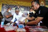 Dirresnarkoba Polda Kalsel Kombes Pol Iwan Eka Putra (dua kiri) mengambil barang bukti narkotika jenis sabu dan ekstasi saat rilis hasil operasi Antik Intan 2020 di Mapolda Kalsel, Banjarmasin, Kalimantan Selatan, Senin (9/3/2020). Terhitung dari tanggal 21 Februari hingga 5 Maret 2020 jajaran Polda Kalimantan Selatan berhasil mengungkap 298 kasus kejahatan peredaran gelap dan penyalahgunaan narkoba dan menangkap 370 pelaku kejahatan serta mengamankan barang bukti sabu seberat 7.413,36 gram dan 14.083 obat-obatan terlarang. Foto Antaranews Kalsel/Bayu Pratama S.