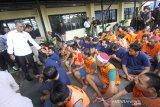Dirresnarkoba Polda Kalsel Kombes Pol Iwan Eka Putra (kiri) memperlihatkan tersangka saat rilis hasil operasi Antik Intan 2020 di Mapolda Kalsel, Banjarmasin, Kalimantan Selatan, Senin (9/3/2020). Terhitung dari tanggal 21 Februari hingga 5 Maret 2020 jajaran Polda Kalimantan Selatan berhasil mengungkap 298 kasus kejahatan peredaran gelap dan penyalahgunaan narkoba dan menangkap 370 pelaku kejahatan serta mengamankan barang bukti sabu seberat 7.413,36 gram dan 14.083 obat-obatan terlarang. Foto Antaranews Kalsel/Bayu Pratama S.