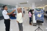 Nasabah diperiksa suhu tubuhnya oleh petugas di Bank Mandiri Banyuwangi, Jawa Timur, Jumat (13/3/2020). Untuk mengantisipasi dan mencegah penyebaran COVID-19, Manajemen Bank Mandiri di Banyuwangi melakukan pemeriksaan suhu tubuh dan menyediakan cairan 'hand sanitizer' bagi nasabahnya. Antara Jatim/Budi Candra Setya/zk