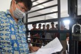 Petugas Pengawasan Sumber Daya Kelautan dan Perikanan provinsi Aceh (kiri) mendata sejumlah nelayan asal Myanmar yang berada di ruang tahanan di Banda Aceh, Aceh, Jumat (13/3/2020). Petugas Pengawasan Sumber Daya Kelautan dan Perikanan (PSDKP) Aceh menahan sebanyak 12 Anak Buah Kapal (ABK) warga Myanmar dan mengamankan dua unit kapal berbendera asal Malaysia dengan nomor lambung PKFB 1099 dan PKFB 776 yang melakukan penangkapan ikan ilegal di perairan Aceh Utara dengan barang bukti kapal tersebut yang saat ini diamankan di pelabuhan Kota Langsa, Aceh. ANTARA FOTO/Ampelsa/ama.