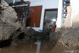 Warga membersihkan rumahnya dari pasir dampak banjir bandang di Sempol, Ijen, Bondowoso, Jawa Timur, Sabtu (14/3/2020). Menurut warga, banjir bandang yang membawa material pasir dan kayu itu dampak dari Gunung Suket yang gundul, hingga menyebabkan ratusan rumah warga tertimbun. Antara Jatim/Budi Candra Setya/zk.