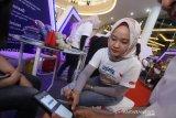 Petugas Bank menjelaskan cara penggunaan Quick Response Indonesia Standard (QRIS) kepada pengunjung pada puncak Pekan QRIS Nasional 2020 di Duta Mall Banjarmasin, Kalimantan Selatan, Sabtu (14/3/2020). Kantor perwakilan Bank Indonesia (BI) Provinsi Kalimantan Selatan menggelar Pekan QRIS untuk mengenalkan dan meningkatkan penggunaan QRIS sebagai sistem pembayaran digital yang lebih mudah dan bisa digunakan oleh semua aplikasi pembayaran dari Penyedia Jasa Sistem Pembayaran (PJSP). Foto Antaranews Kalsel/Bayu Pratama S.