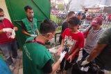 Relawan  semprotkan hand sanitizer ke tangan penonton pada laga PSM vs Barito
