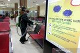 Petugas Kantor Kesehatan Pelabuhan (KKP) melakukan penyemprotan cairan disinfektan di ruang tunggu terminal kedatangan dan keberangkatan di Bandara Internasional Sultan Iskandar Muda (SIM), Aceh Besar, Aceh, Senin (16/3/2020). PT. Angkasa Pura  selaku pengelola  bandara SIM bekerjasama dengan KKP melakukan penyemprotan disinfektan guna mencegah penularan Corona Virus Disease 2019 (COVID-19). Antara AcehIrwansyah Putra.