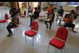 Warga duduk dengan jarak yang diatur saat menunggu giliran untuk mengurus dokumen di Mal Pelayanan Publik Graha Sewaka Dharma, Denpasar, Bali, Kamis (19/3/2020). Pemerintah Kota Denpasar memberlakukan