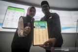 Gubernur Jawa Barat Ridwan Kamil (kanan) bersama Ketua Jabar Bergerak Atalia Praratya (kiri) menunjukan aplikasi Pusat Informasi dan Koordinasi COVID-19 (Pikobar) setelah di luncurkan di Jabar Command Center, Bandung, Jawa Barat, Jumat (20/3/2020). Pemerintah Provinsi Jawa Barat meluncurkan aplikasi Pikobar guna memberikan layanan dan informasi kepada masyarakat terkait COVID-19. ANTARA JABAR/Raisan Al Farisi/agr