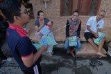 Aparatur desa menjelaskan cara penanggulangan COVID-19 saat sosialisasi ke rumah warga di Denpasar, Bali, Jumat (20/3/2020). Kegiatan sosialisasi tersebut untuk mengedukasi dan memberikan informasi kepada masyarakat agar tanggap serta sigap dalam pencegahan penyebaran COVID-19 atau Virus Corona. ANTARA FOTO/Nyoman Hendra Wibowo/nym.