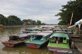 Sejumlah kelotok (perahu bermesin) sandar di sungai Martapura di Kawasan Siring Piere Tandean, Banjarmasin, Kalimantan Selatan, Sabtu (21/3/2020). Kawasan tersebut di tutup sementara oleh Pemerintah Kota Banjarmasin sebagai upaya pencegahan penyebaran virus COVID-19. Foto Antaranews Kalsel/Bayu Pratama S.