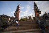 Seorang umat Hindu berjalan menuju tempat persembahyangan di Pura Agung Jagatnatha Wana Kertha, Palu, Sulawesi Tengah, Selasa (24/3/2020). Mengikuti anjuran pemerintah, Parisada Hindu setempat meniadakan ritual persembahyangan bersama menyambut hari raya Nyepi untuk mencegah penyebaran Virus Corona, kecuali dilakukan sendiri-sendiri dan tidak secara berkelompok. ANTARAFOTO/Basri Marzuki/nym.