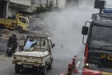 Petugas kepolisian menyemprotkan disinfektan menggunakan mobil armor water canon di Kota Tasikmalaya, Jawa Barat, Selasa (24/3/2020). Penyemprotan disinfektan sekaligus imbauan kepada warga disepanjang jalur pusat kota Tasikmalaya sebagai upaya pemerintah setempat untuk mencegah penyebaran wabah COVID-19. ANTARA JABAR/Adeng Bustomi/agr