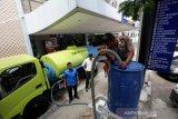 Personil Polresta Banda Aceh membantu petugas mengisi air ke dalam tempat penampungan untuk cuci tangan di depan Mall Pelayanan Publik (MPP) pasar Aceh, Banda Aceh, Aceh, Selasa (24/3/2020). Tim pencegahan dan penanggulangan virus Corona (COVID-19) Pemerintah Kota Banda Aceh menyediakan fasilitas cuci tangan yang dilengkapi wastafel dan sabun cuci di lokasi keramaian serta area publik sebagai upaya mencegah penularan virus tersebut. Antara Aceh/Irwansyah Putra.