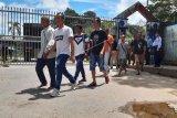Sejumlah Pekerja Migran Indonesia (PMI) melintasi pintu pagar setibanya di Pos Lintas Batas Negara (PLBN) Entikong, Kabupaten Sanggau, Kalbar, Sabtu (21/3/2020). Pasca