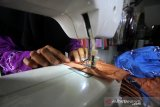 Penyandang disabilitas menyelesaikan pembuatan masker sasirangan berbahan pewarna alami yang ramah lingkungan di Showroom Yayasan Rumah Kreatif dan Pintar di Banjarmasin, Kalimantan Selatan, Rabu (25/3/2020). Masker buatan penyandang disabilitas tersebut untuk di bagikan gratis kepada ojek online, petugas kebersihan serta masyarakat yang sangat memerlukan sebagai bentuk kepedulian dalam upaya mencegah penyebaran virus corona (COVID-19). Foto Antaranews Kalsel/Bayu Pratama S.