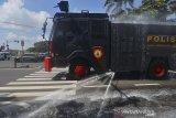 Petugas kepolisian menyemprotkan disinfektan menggunakan mobil armor water canon Polres Tasikmalaya Kota di Kabupaten Ciamis, Jawa Barat, Rabu (25/3/2020). Penyemprotan disinfektan tersebut dilakukan untuk mencegah penyebaran wabah virus corona atau COVID-19. ANTARA JABAR/Adeng Bustomi/agr