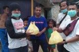 Relawan SR bagi-bagi cairan disinfektan kepada warga Karimun