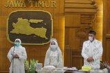 Gubernur Jawa Timur Khofifah Indar Parawansa (kiri) menyampaikan sambutan disela-sela acara resepsi pernikahan Yavuz Ozdemir (kanan) dan Irra Chorina Octora (tengah) di Gedung Negara Grahadi, Surabaya, Jawa Timur, Rabu (25/3/2020). Gubernur Jawa Timur Khofifah Indar Parawansa menggelar resepsi pernikahan dua pasang pengantin Yavuz Ozdemir-Irra Chorina Octora serta Amal Fatchullah-Diana Anggraini yang hanya dihadiri pihak keluarga mempelai guna menghindari pertemuan dengan orang banyak dan meminimalkan penyebaran COVID-19. Antara Jatim/Moch Asim/zk.