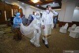 Salah satu pasangan pengantin Yavuz Ozdemir (kanan) dan Irra Chorina Octora (tengah) berjalan beriringan disela-sela acara resepsi pernikahannya di Gedung Negara Grahadi, Surabaya, Jawa Timur, Rabu (25/3/2020). Gubernur Jawa Timur Khofifah Indar Parawansa menggelar resepsi pernikahan dua pasang pengantin Yavuz Ozdemir-Irra Chorina Octora serta Amal Fatchullah-Diana Anggraini yang hanya dihadiri pihak keluarga mempelai guna menghindari pertemuan dengan orang banyak dan meminimalkan penyebaran COVID-19. Antara Jatim/Moch Asim/zk.