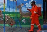 Relawan menyemprotkan cairan disinfektan di sebuah sekolah di Ngawi, Jawa Timur, Kamis (26/3/2020). Penyemprotan yang diprioritaskan di kawasan sekolah dan tempat umum tersebut untuk mengantisipasi penyebaran virus Corona yang menurut data Dinas Kesehatan setempat jumlah Pasien Dalam Pengawasan (PDP) sebanyak 4 orang. Antara Jatim/Ari Bowo Sucipto/zk