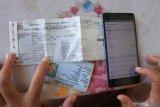 Seorang warga membayar pajak kendaraan bermotor dari rumah secara daring atau online di Panarukan, Situbondo, Jawa Timur, Kamis (26/3/2020). Pembayaran secara online itu karena diliburkannya pembayaran secara langsung melalui Samsat untuk mencegah penularan Covid-19. Antara Jatim/Seno/zk