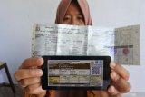 Seorang warga memperlihatkan bukti pelunasan pajak kendaraan bermotor yang dibayar secara daring atau online dari rumah di Panarukan, Situbondo, Jawa Timur, Kamis (26/3/2020). Pembayaran secara online itu karena diliburkannya pembayaran secara langsung melalui Samsat untuk mencegah penularan Covid-19. Antara Jatim/Seno/zk