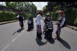 Pecalang atau petugas keamanan adat Bali memeriksa sejumlah warga yang melintas di Tabanan, Bali, Kamis (26/3/2020). Penjagaan dilakukan di setiap perbatasan desa / kota dengan melibatkan unsur pecalang, TNI dan Polri untuk mengurangi lalu lalang orang pascaimbauan gubernur Bali agar masyarakat tetap berada di rumah untuk mencegah penyebaran COVID-19. ANTARA FOTO/Nyoman Hendra Wibowo/nym