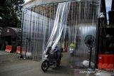 Seorang anggota kepolisian memasuki lorong dekontaminasi di Polda Jabar, Bandung, Jawa Barat, Kamis (26/3/2020). Polda Jabar mewajibkan seluruh kendaraan dan orang yang akan masuk untuk melewati lorong yang menyemprotkan cairan disinfektan guna mencegah penyebaran COVID-19 di lingkungan Mapolda Jabar. ANTARA JABAR/Raisan Al Farisi/agr