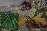 Pekerja menyelesaikan pembuatan masker dirumah produksi konveksi Purnama Kampung Mancogek, Kota Tasikmalaya, Jawa Barat, Kamis (26/3/2020). Pelaku usaha konveksi memproduksi 45 lusin masker per harinya dengan harga jual Rp 35.000 per lusin. ANTARA JABAR/Adeng Bustomi/agr