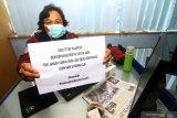 Jurnalis Harian Pontianak Post Donatus Budiono memperlihatkan kertas berisi himbauan bertajuk 'Di Rumah Aja' di ruang redaksi Graha Pena Pontianak, Kalimantan Barat, Senin (23/3/2020). Himbauan untuk masyarakat supaya melakukan pekerjaan dan berkegiatan di rumah saja tersebut bertujuan untuk memutuskan rantai penularan virus Covid-19. ANTARA FOTO/Jessica Helena WuysangANTARA FOTO/JESSICA HELENA WUYSANG (ANTARA FOTO/JESSICA HELENA WUYSANG)