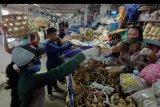 Pedagang bumbu melayani pembeli saat dibukanya kembali Pasar Badung pascapenutupan terkait imbauan tidak keluar rumah di Denpasar, Bali, Jumat (27/3/2020). Pemerintah Kota Denpasar mulai menerapkan sistem belanja lewat internet di pasar tradisional terbesar di Bali tersebut untuk membatasi lalu lalang orang sebagai upaya pencegahan penyebaran COVID-19. ANTARA FOTO/Nyoman Hendra Wibowo/nym