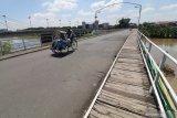 Warga melintas di atas Jembatan Lama Kediri (Brug Over Den Brantas de Kediri) yang merupakan jembatan berkonstruksi besi pertama di Jawa peninggalan kolonial Belanda di Kota Kediri, Jawa Timur, Kamis (26/3/2020). Kegiatan perayaan ulang tahun ke-151 jembatan cagar budaya tersebut urung dilakukan oleh pemerintah daerah setempat untuk mengurangi interaksi sosial guna menanggulangi penyebaran COVID-19. Antara Jatim/Prasetia Fauzani/zk
