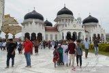 Jamaah berjalan seusai melaksanakan Salat Jumat di Masjid Raya Baiturrahman, Banda Aceh, Aceh, Jumat (27/3/2020). Pelaksanaan Salat Jumat di Masjid Raya Baiturrahman itu masih tetap berlangsung namun jumlah jamaahnya berkurang dibanding sebelumnya, meski di sebagian daerah lainnya sudah menghentikan kegiatan salat jumat guna mengantisipasi penyebaran virus COVID-19.Antara Aceh/Ampelsa.