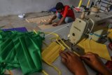 Pekerja menyelesaikan pembuatan masker dirumah produksi konveksi Purnama Kampung Mancogek, Kota Tasikmalaya, Jawa Barat, Kamis (26/3/2020). Akibat penyebaran pandemi virus Corona (COVID-19) berdampak pada orderan pembuatan seragam sekolah sepi pembeli sehingga pelaku usaha konveksi beralih profesi membuat masker berbahan kain oxford, dengan memproduksi 45 lusin masker per hari, sedangkan permintaan masker mencapai 500 lusin per hari dengan harga jual Rp35.000 per lusin. ANTARA FOTO/Adeng Bustomi/hp.