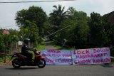 Warga melintas di dekat akses masuk kampung yang ditutup di kawasan Pakem, Sleman, D.I Yogyakarta, Jumat (27/3/20). Sejumlah kampung di Kecamatan Pakem, Sleman menutup sejumlah akses masuk kampung dengan bambu yang diberi tulisan