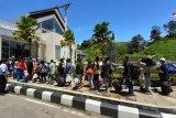 Sejumlah Pekerja Migran Indonesia (PMI) antri memasuki gedung Pos Lintas Batas Negara (PLBN) Entikong, Kabupaten Sanggau, Kalbar, Jumat (27/3/2020). Sebanyak 62 PMI bermasalah (overstay dan tidak memiliki ijin kerja) yang telah selesai menjalani masa hukuman di Depot Imigresen Semunjan (Serian), serta empat WNI repatriasi yang mendapat pendampingan dari KJRI Kuching Sarawak, dipulangkan Pemerintah Malaysia melalui PLBN Entikong. ANTARA FOTO/Agus Alfian/jhw/ama.