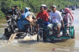Sejumlah pengedara memanfaatkan jasa angkut kendaraan roda dua untuk menembus jalan yang terendam banjir di Desa Layung, Kecamatan Bubon, Aceh Barat, Aceh, Minggu (29/3/2020). Warga yang berada di kawasan tersebut memanfaatkan banjir untuk menyewakan jasa angkut kendaraan melintasi banjir dengan tarif Rp10.000 sampai Rp 20.000 per sekali angkut kendaraan tergantung jarak. Antara Aceh/Syifa Yulinnas.