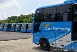 Seorang warga melintas di depan bis umum Trans Koetaradja di gudang terminal Batoh, Banda Aceh, Aceh, Senin (30/3/2020). Pemerintah Aceh menggudangkan seluruh armada angkutan kota Trans Kuetaradja sejak Jumat (27/3/2020) hingga batas belum ditentukan untuk mencegah penyeberan Virus COVID-19. Antara Aceh/Ampelsa.