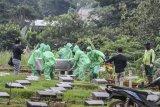 Petugas pemakaman membawa peti jenazah pasien COVID-19 di TPU Pondok Ranggon, Jakarta, Senin (30/3/2020). Juru bicara pemerintah untuk penanganan COVID-19 Achmad Yurianto per Senin (30/3/2020) pukul 12.00 WIB menyatakan jumlah pasien positif COVID-19 di Indonesia telah mencapai 1.414 kasus, pasien yang telah dinyatakan sembuh sebanyak 75 orang, sementara kasus kematian bertambah delapan orang dari sebelumnya 114 orang menjadi 122 orang. ANTARA FOTO/Muhammad Adimaja/nym.