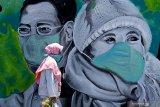 MURAL LAWAN CORONA. Warga melintas di depan mural Lawan Corona di Jalan Wonokromo, Surabaya, Jawa Timur, Kamis (26/3/2020). Mural karya Serikat Mural Surabaya tersebut merupakan media edukasi kepada warga agar mencegah potensi penyebaran virus corona atau COVID-19, salah satunya dengan cara memakai masker saat beraktivitas di luar rumah. Antara Jatim/Moch Asim/zk