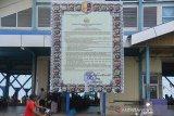 Seorang warga melintas di depan papan Maklumat Polri yang ditempatkan di Pelabuhan Perikanan Kutaraja, Lampulo, Banda Aceh, Aceh, Rabu (1/4/2020). Penempatan papan Makulumat Polri itu merupakan upaya pemerintah mensosialisasikan ke pada masyarakat, termasuk daerah kawasan pesisir meliputi pelabuhan perikanan tempat terjadi perkumpulan nelayan untuk mencegah penyeberan virus COVID-19. Antara Aceh/Ampelsa.