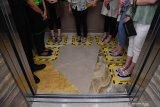 JAGA JARAK DI LIFT. Pengunjug menaiki lift yang telah dipasangi garis batas setiap pengguna di Tunjungan Plaza, Surabaya,  Jawa Timur, Rabu (18/3/2020). Pembatasan tersebut dilakukan guna mengantisipasi penyebaran Virus Corona (COVID-19). Antara Jatim/Zabur Karuru