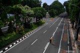 PENUTUPAN JALAN DI SURABAYA. Petugas kebersihan menyapu jalan di Jalan Darmo yang ditutup, Surabaya, Jawa Timur, Sabtu (28/3/2020). Penutupan sejumlah jalan di Surabaya tersebut bertujuan agar ruas jalan itu terbebas dari segala bentuk aktifitas warga dan kendaran guna mencegah penyebaran Virus Corona (COVID-19). Antara Jatim/Zabur Karuru