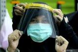 PRODUKSI FACE SHIELD. Relawan mencoba memakai alat pelindung wajah (Face Shield) di Departemen Desain Produk Industri, Institut Teknologi Sepuluh Nopember (ITS), Surabaya, Jawa Timur, Senin (23/3/2020). Face Shield buatan ITS tersebut akan didonasikan kepada tenaga medis dalam menangani secara langsung pandemi COVID-19 yang secara nasional jumlah target kebutuhannya mencapai 270.000. Antara Jatim/Moch Asim/zk