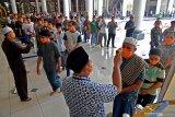 SHALAT JUMAT SURABAYA. Umat muslim  mengenakan masker mengantri memeriksakan suhu tubuh ketika memasuki Masjid Nasional Al Akbar Surabaya untuk melaksanakan shalat Jumat, Surabaya, Jawa Timur, Jumat (20/3/2020). Masjid tersebut tetap melaksanakan shalat Jumat dengan berbagai aturan seperti setiap jamaah wajib mengenakan masker, pemeriksaan suhu tubuh dan shaf yang berjarak satu meter.  Antara Jatim/Zabur Karuru/zk