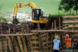 TANGGUL JEBOL DI KEDIRI. Warga memperbaiki tanggul yang jebol pasca banjir di Desa Jatikapur, Kediri, Jawa Timur, Kamis (5/3/2020). Sedikitnya tiga titik tanggul di wilayah itu jebol diterjang banjir kiriman dari kawasan gunung Wilis. Antara Jatim/Prasetia Fauzani/zk