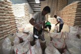 Pekerja mengemas beras di Pasar Induk Beras Cipinang, Jakarta, Selasa (31/3/2020). Perum Bulog pastikan stok beras mencukupi untuk mengatasi kebutuhan lonjakan pangan dalam kondisi tidak terduga, sekaligus dalam menyambut Ramadan dan Idul Fitri. ANTARA FOTO/Indrianto Eko Suwarso/nz